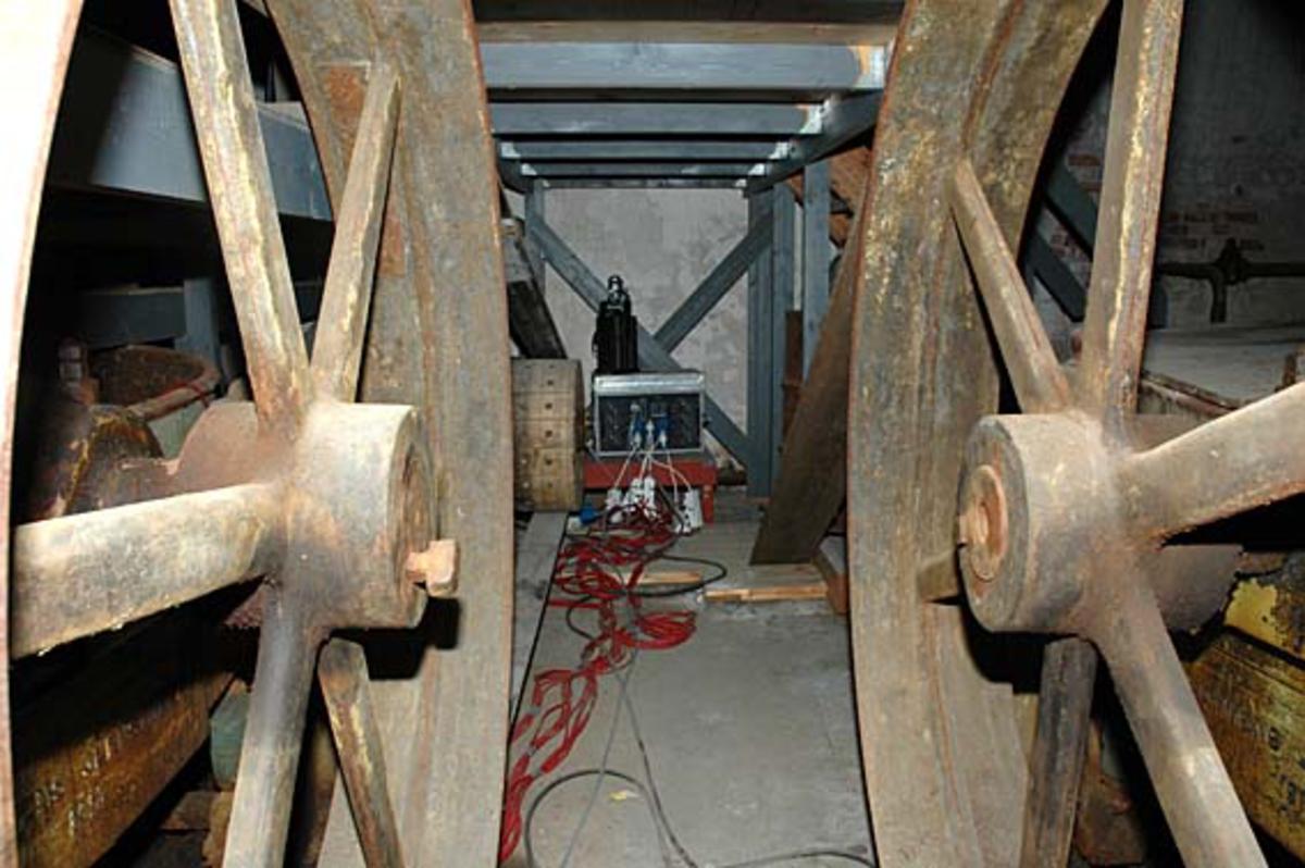 I mellom drivhjulene til hollenderne, står en strømforsyningskasse for teaterbelysning, for dagens aktiviteter på Klevfos Industrimuseum.  Løten. Ådalsbruk.