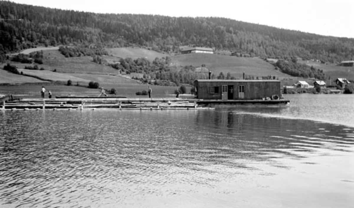Ambulerende soppeappatat, fotografert i den nordre delen av Mjøsa, nærmere bestemt ved Korsvika på Brøttum.  Vi skimter Brøttum jernbanestasjon i bakgrunnen til høyre med Freng-gardene i lia ovenfor.  Soppeapparatet var en langstrakt konstruksjon som fløt på pongtonger.  Sentralt på denne flytende innretningen var det sannsynligvis en eller to kjerrater, som trakk tømmerstokker fra enden av anlegget opp mot en plattform, der det sto fløtere og dyttet dem ned et skråplan på sida mot et avgrenset basseng, et soppe- eller mosekammer, der tømmeret ble buntet med vaierbindsel, slik at det kunne slepes videre sørover Mjøsa uten nevneverdig svinn.  Brakka på den ytre enden av soppeapparatet inneholdt sannsynligvis både motorrrom (trekkraft til kjerraten) og kvilerom for mannskapene som betjente soppeapparatet. En innretning som denne kunne lett slepes til steder der det ble levert løstømmer ved strendene, og til elveutløp der man lenset inn tømmer i mengder som ikke var store nok til at det svarte seg å investere i permanente soppeapparater.