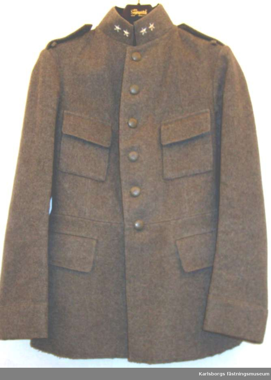 Vapenrock m/1923, Löjtnant, Kungliga Älvsborgs Reg I 15, Borås. Gråbruntgrönt kommiss. Vapenrocken har ståndkrage med gradbeteckning för kapten av silverfärgat metall. Kragen är fodrad med polyamidtrikå och har två hyskor med hake. Axelklaffar av samma tyg och färg som vapenrocken och med 15 i gult tyg och två knappar med reg:tes vapen diam. 24 mm, h 8 mm. Gråmålade av metall. Två bröstfickor med raka lock under ficklock knapp med knapphål. Två stycken sidfickor insydda med raka lock. Ärmen har fast uppslag. Sprund bak med två knappar i midjesömmen, med reg:tes vapen. Stämplar på livfodret, krona I 15 ACB 1925 11 c 941. Fodret har två fickor. Gåva till museet och använd av läjtnant Lennart Nyman.