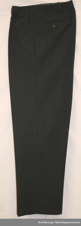 Storlek: C 108 Långbyxor av mörkblått tyg. Löst midjeband medknapp och knapphål. Bakfickor med knapp o knapphälla. Har tillhört Rickard Lilja.