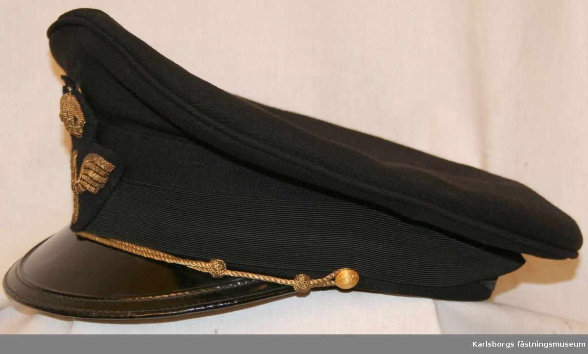 Storlek: 56 Skärmmössa m/1930 av mörkblått tyg mössband av svart räfflat silke. Svart lackerad skärm, försedd med hakrem av guldsnodd fäst vid två 14 mm uniformsknappar samt flygemblem.