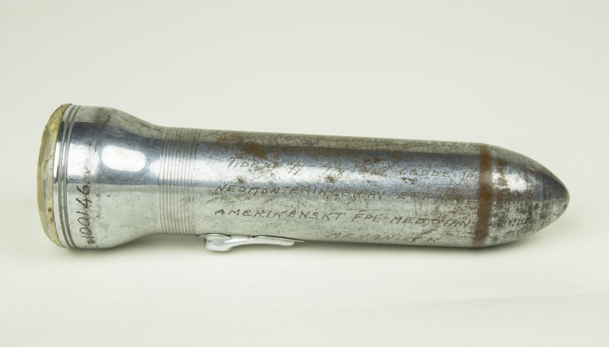 Stavlampa, batteri. Handskriven text på stavlampan: LIBERATOR Nr 42-100146. Därefter följer en redogörelse för nedmonteringen av ett nödlandat amerikanskt flygplan 1944. Texten är endast delvis läsbar.