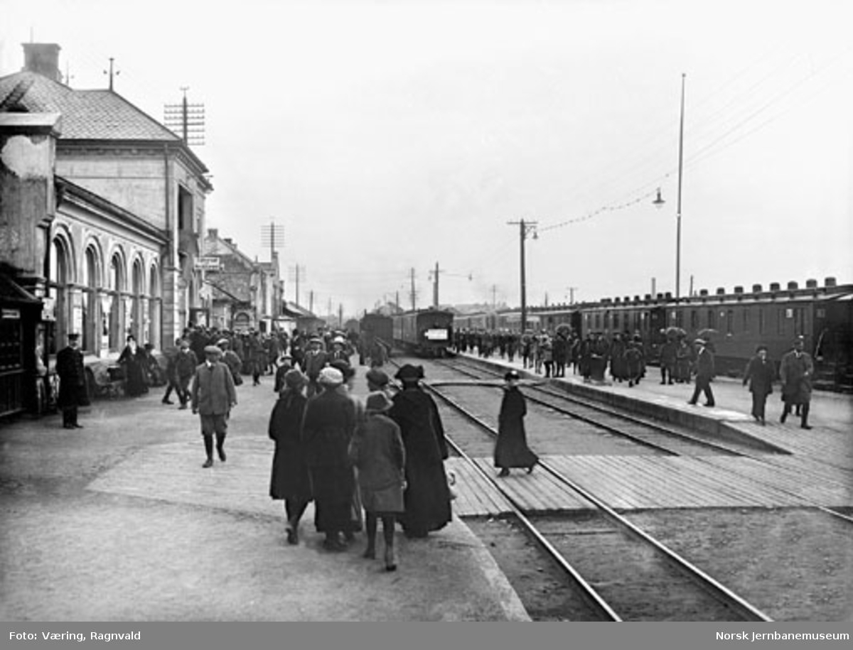 Hamar stasjon med reisende, det smalsporede Trondheimstoget og normalsportoget fra Oslo