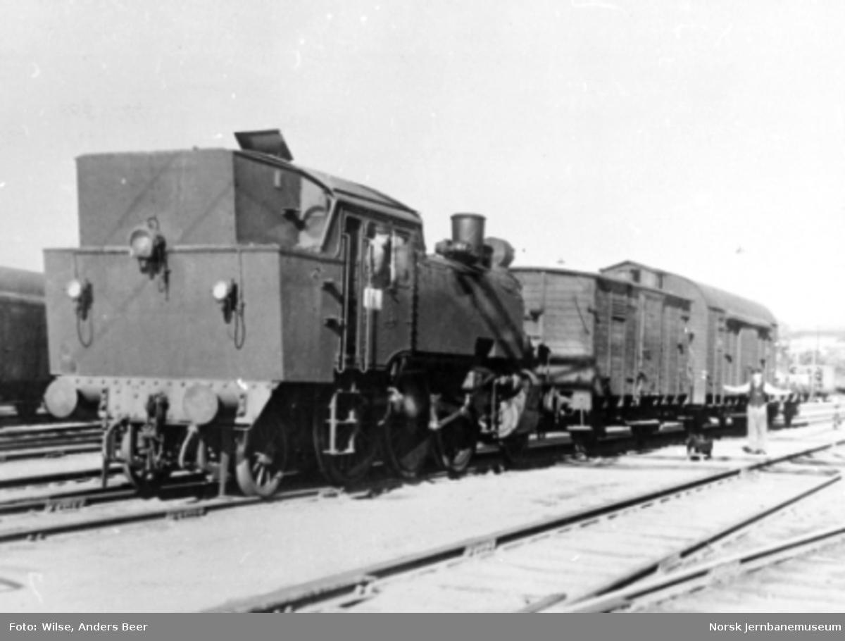 Damplokomotiv type 32b nr. 13 under skifting; en jernbanemann gir stoppsignal