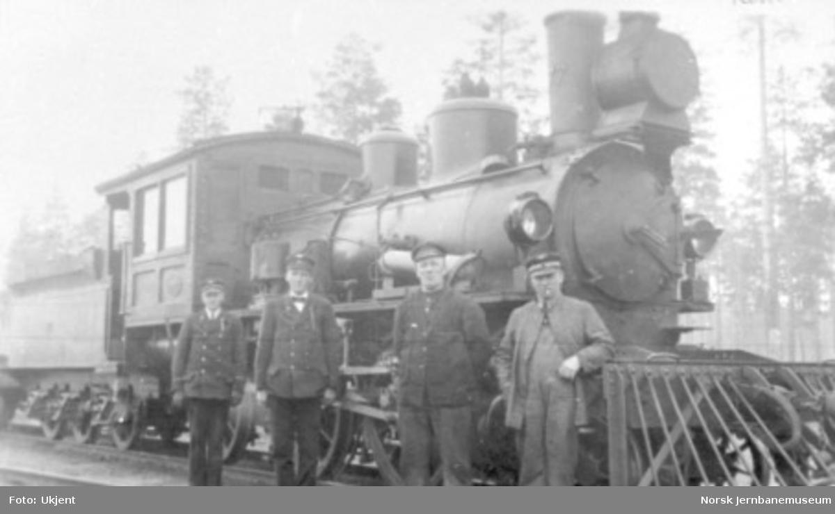 Damplokomotiv type XXIIId nr. 77 foran kistog på Elverum stasjon; togpersonalet poserer i forgrunnen