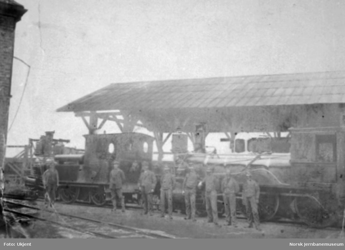 To damplokomotiver : type V og XIII, med personale ved lokomotivstallen på Skien G