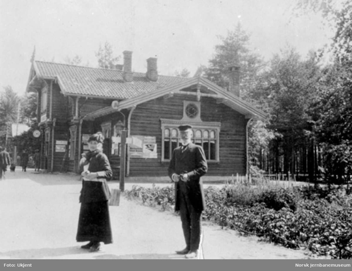 Byglandsfjord stasjonsbygning med et par i forgrunnen