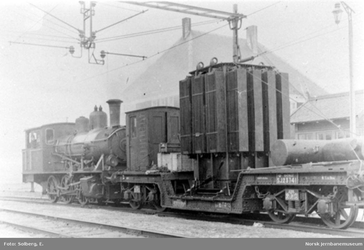 Ofotbanens elektrifisering : transformator til transformatorstasjonen på Katterat stasjon opplastet på svensk dyplastevogn litra Q nr. 23741 bak damplokomotiv nr. 159
