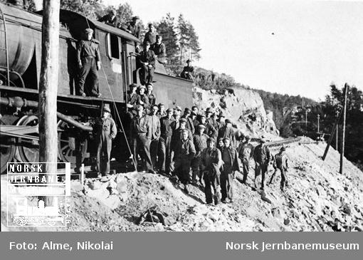 Gruppebilde av en stor gjeng banearbeidere ved siden av damplokomotiv type 33 nr. 324 på sørlandsbaneanlegget