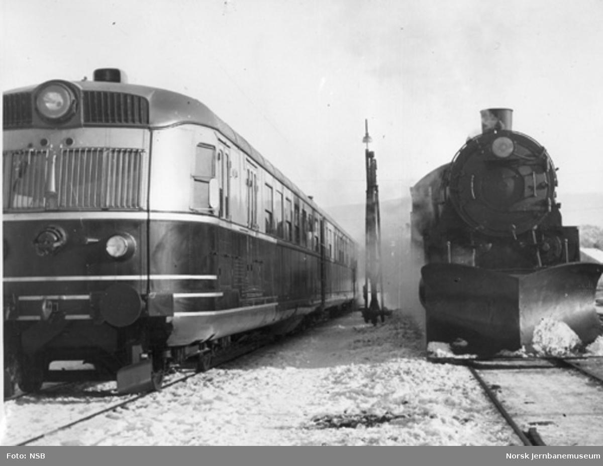 Ekspresstogsett type 88 ved siden av et damplokomotiv