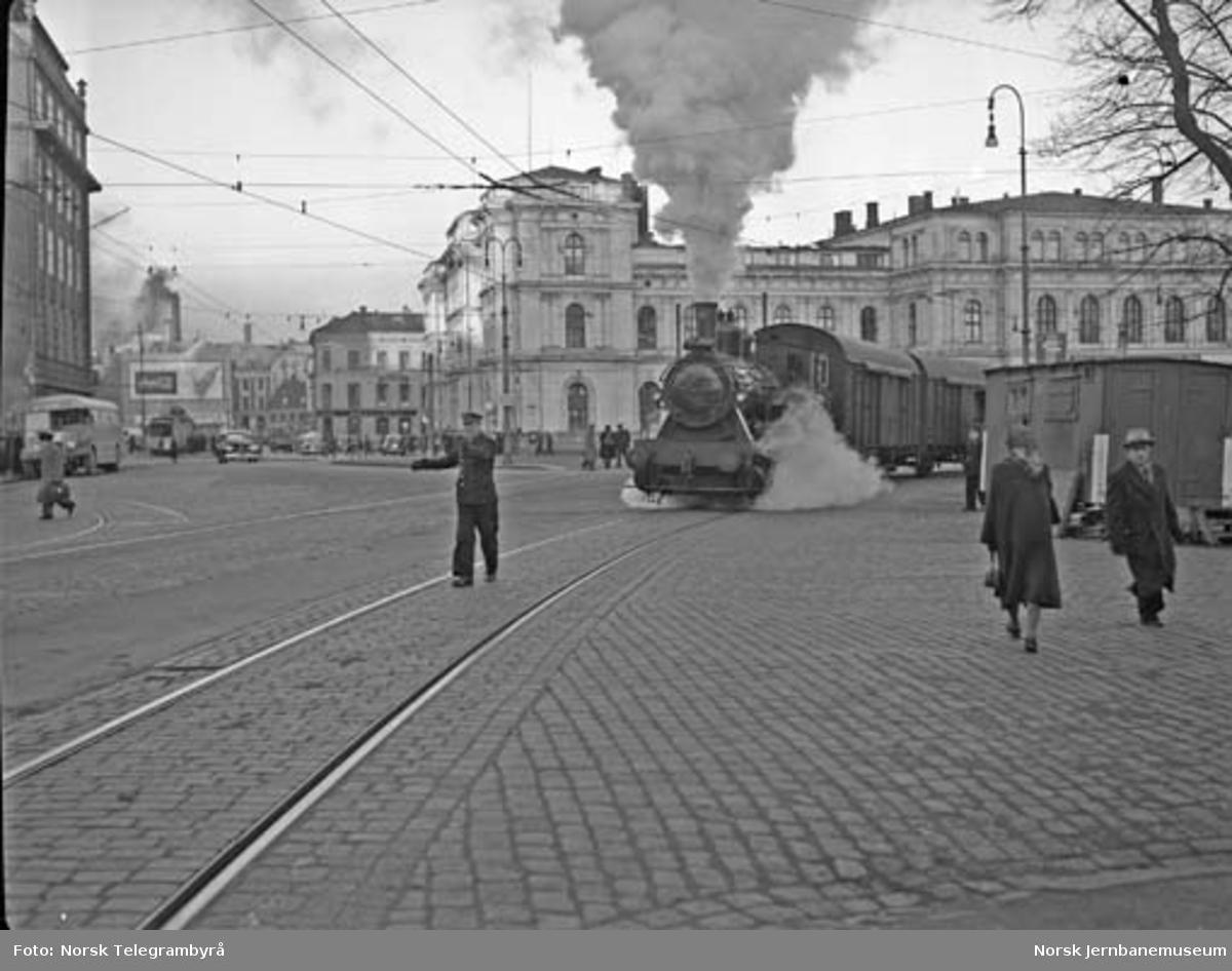 Damplokomotiv type 23b med havnekippen utenfor Østbanen : en skiftekonduktør går foran