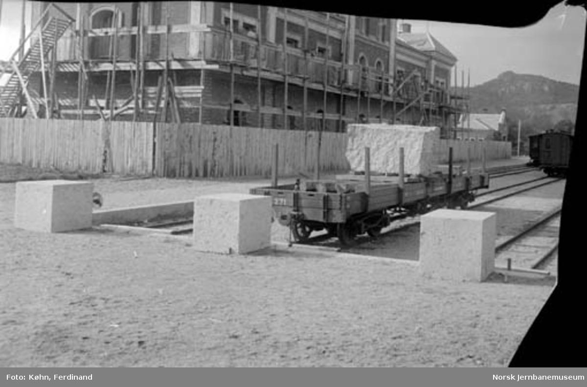 Kongesteinen ankommer Kristiansand stasjon på godsvogn : stasjonsbygningen under oppførelse i bakgrunnen