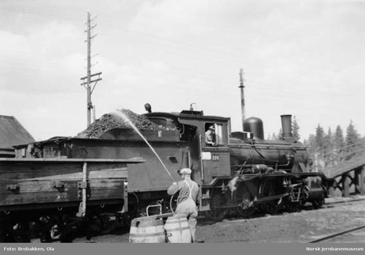 Lokstallbetjent John M. Ryen spyler kullene på damplokomotiv nr. 226 på Koppang stasjon