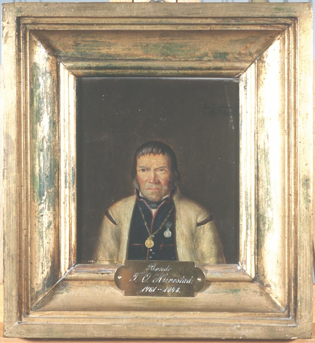 Portrett av Tallev O. Huvestad. Hvit trøye (jakke) og mørk vest m/røde kanter.  Frederik VI's erindringsmedalje i kjede om halsen, Danebrog eller Borgerdådsmedaljen på brystet.