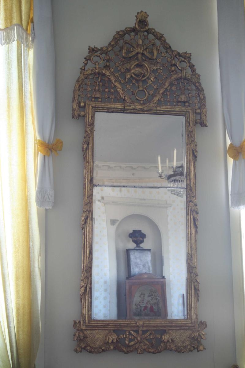 Louis XVI speil med delt glass. Stor forgylt ramme med bladranker og gitter, papegøye i ring h. i sløyfe. ca. 1780 - 1800.