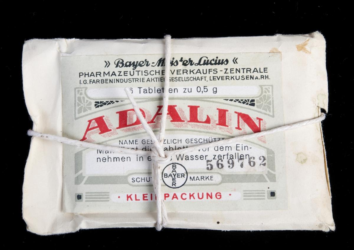 Uåpnet tabletteske i en liten konvolutt med hyssing rundt. På baksiden streifetikett med teksten: Garantipakning for Norge.