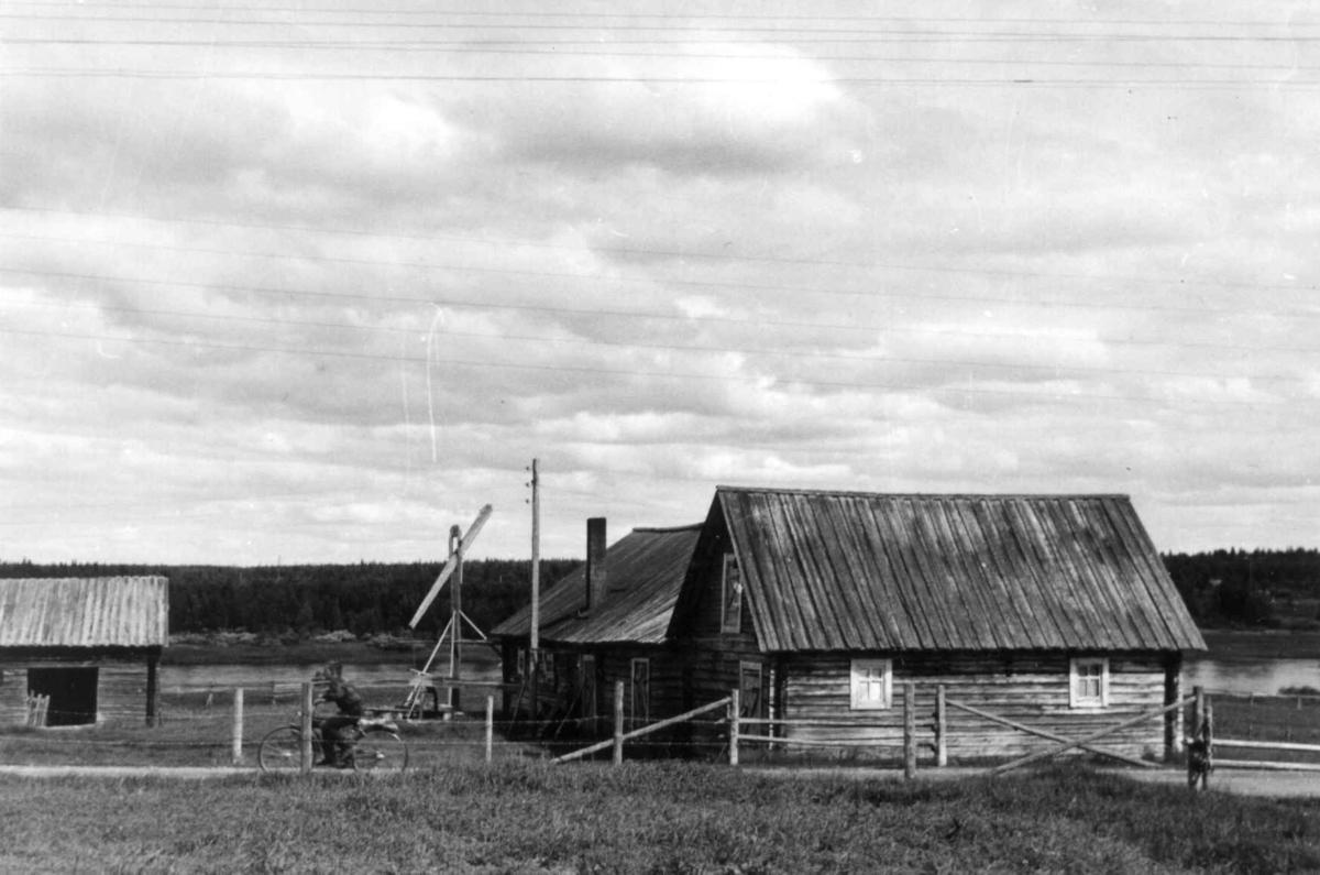 Mattigården med fjøsbygning, brønn og bod for oppbevaring av klær og ved. En syklist på veien. Lainio 1958.