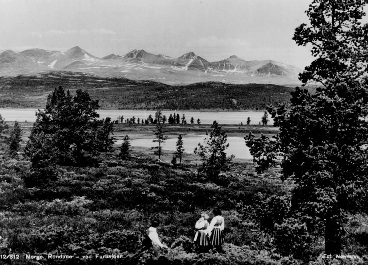 Avfotografert postkort. Tre kvinner i rondastakk ved Furusjøen. I bakgrunnen sees Rondane.