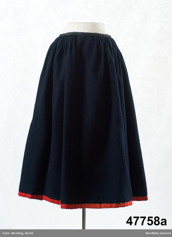 Kvinnodräkt a-d  a. Kjol av mörkblå vadmal med rött kantband b. Livstycke av halvylle med ljus linvarp och täckande inslag i kypert av tunt ullgarn smalrandigt i övervägande 2 olika nyanser rött samt ljusgrönt, svart och vitt. I de gröna ränderna gula och röda hoppor.
