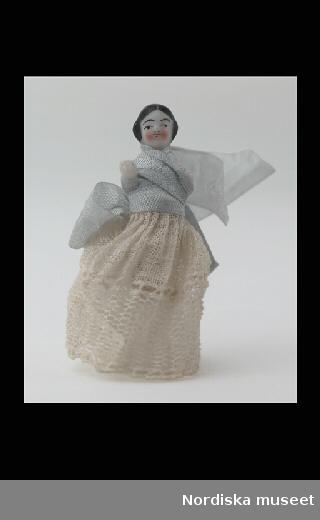 """Inventering Sesam 1996-1999: L 3,5  cm Docka, """"Frozen Charlotte"""", av porslin, svart målat hår. Klädd i lång spetskjol och överkroppen inlindad i blått sidenband.  Vänster arm avslagen, höger hand skadad. Små dockor av denna typ kan även användas som grötdockor. Hör troligen till dockskåp inv 126.349. Birgitta Martinius 1996"""