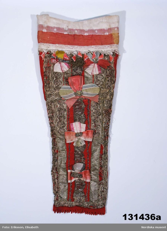 """Huvudliggaren: """"a-c Dopdräkt, bestående av påse och mössa av rött ylle med silverband, spetsar, rosetter m.m.""""  A.Doppåse, B. Dopmössa C+. Tre boksidor, vitlöksklyfta och lan av gulmetall. A. Doppåse av rött tuskaftat ylletyg s.k. kamlott, påsen avsmalnande nedåt. Framsidan täckt med rader av silvergaloner och silverspetsar och i en rad i mitten 5 stora rosetter av sidenband i rosa, ljusgrönt och vitt med en bit hopsnodd silverspets i mitten. Övre delen av påsen av mycket fin linnelärft täckt med ett brett rosarött sidenband, samt en rad med trädd tyllspets tillsammans med en uddkant med vitbroderi, i tyllspetsens uddar är fäst små tofsar av rosa sidenband. kring halsöppningen omvikt  remsa av vit trådgardin  med invävda prickar. I nederkanten en uddklippt remsa av den röda kamlotten. Påsen är vadderad på framstycket och fodrad med oblekt linnelärft. Anm. Silverspetsarna slitna, enstaka hål efter skadeinsekter på baksidan.  B. Dopmössa av röd sidenrips, flickmodell med två sidstycken och ett mittstycke, sömmarna markerade med smala silverspetsar. Runt framkanten 2 cm bred silvergalon. Mössan lätt vadderad troligen med linblånor och fodrad med 2 olika kattuntryck, ett småmönstrat med romber i rött o brunt på ljus botten och ett med blommönster i samma färgställning. Kring innerkanten fasttråcklad remsa av linong kantad med tunn maskingjord spets som tittar fram som rysch kring ansiktet. Knytband av rosa sidenband. I ena änden på bandet finns en svart stämpel som kan vara en tillverkarstämpel eller hallstämpel men nu är oläslig.  C+. Längst ned i botten på påsen låg ett litet """"paket"""" bestående av 3 blad ur en religiös skrift med rubriktexten: Berättelser om de obotfärdigas förhinder"""". Pappren omslöt dels en vitlöksklyfta, dels en liten bit bladguld(?) som avsetts skydda det odöpta spädbarnet. Berit Eldvik april 2006  En vitlök kunde gömmas i dopdräkten som skydd mot de onda makter som hotade det lilla hedniska barnet under färden till kyrkan, innan det genom dopet fåt"""