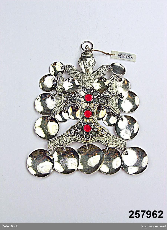 """Huvudliggaren (år 1959-1960): """"257.962 Hängsmycke, kors med änglakrön, av förgyllt silver med filigran och 3 röda stenar samt 19 st runda skålade hängen, på baksidan 'PAS / HOD'. H. 12,5 cm. Tillv. Niclas Blekberg d.ä. eller d.y., Karlshamn. I. 1959 2/7 Fru Ragnhild Gauffin, Stockholm. Inv. nr. 257.956-258.000 = 1.055:-""""  Striglakors, gjutet i silver med förgylld framsida och tre runda, röda glasstenar infattade i en filigrandekor som är nitad vid korset. Krön i form av ängel, vid vilken hängöglan är fäst.. Från ängelns vingar, korsarmarna och svicklarna hänger 19 stycken förgyllda, skålformade hängen. På korsets baksida graverade monogram, PAS och HOD. Mästarstämpel NBB (slagen två gånger), Niclas Bleckberg d. ä. (verksam 1779-1806) i Karlshamn och trekronorstämpel. Jämför inv. nr. 115.718 A-B. /Conni Hultberg/Marie Tornehave 2008."""