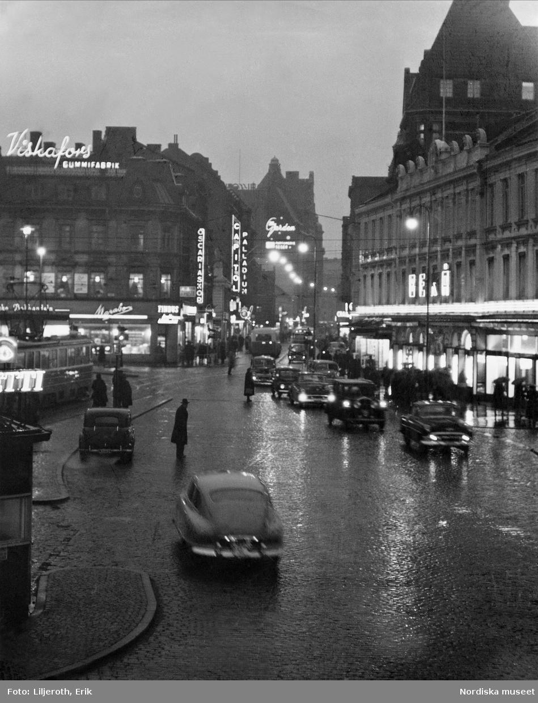 Regn, skymning, trafik och neonskyltar på Södergatan, Malmö.