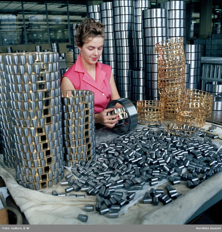 Interiör från SKF:s kullagerfabrik i Göteborg. Kvinna monterar ihop delar till kullager.