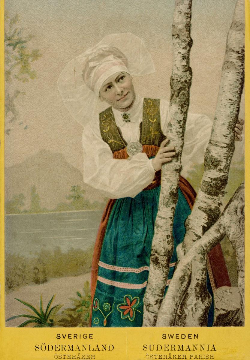 Kolorerat porträttfotografi av som kvinna tittar fram bakom björkstammar. Hon är klädd i folkdräkt från Österåker i Södermanland. Dräkten sydd som en nationalromantisk rekonstruktion av originalplagg kring 1900.