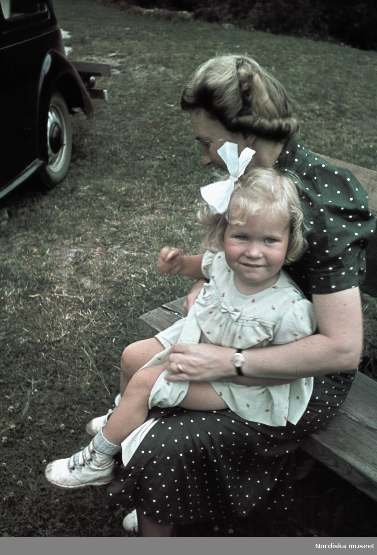 Flicka med rosett i håret sitter i en kvinnas knä.
