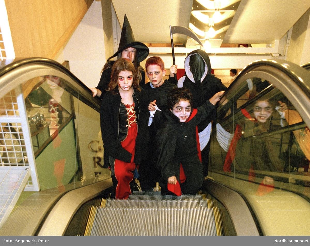 Utklädda barn i rulltrappa. Förberedelser och firande av Halloween.