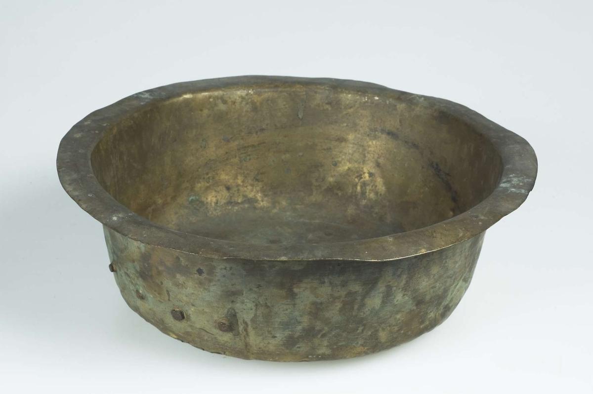 Skål av mässing, lagad i botten med en kopparnit och handgjorda nitar.