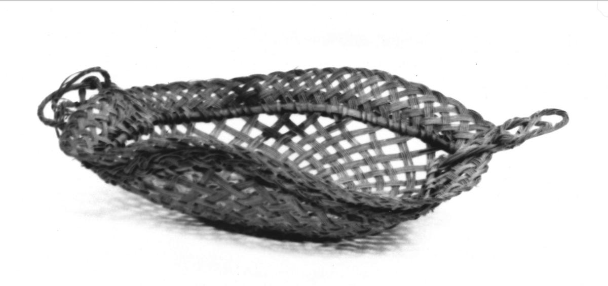 Brödkorg av fin rottflätning. Rektangulär form med rundade hörn och uppböjda kanter. I botten cirkelrund tät vävning och flätning, i övrigt gles gallerveksartad flätning av fem varandra åtföljande rottrådar. På kortsidorna snodda handtag.