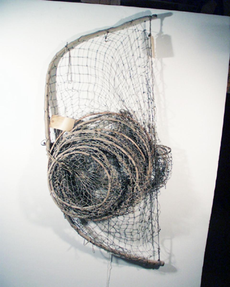 Gäddryssja, handbunden av bomullsgarn i strutform. Garnet hålls ut av bågar av gran. Nio runda bågar och en halvbåge.