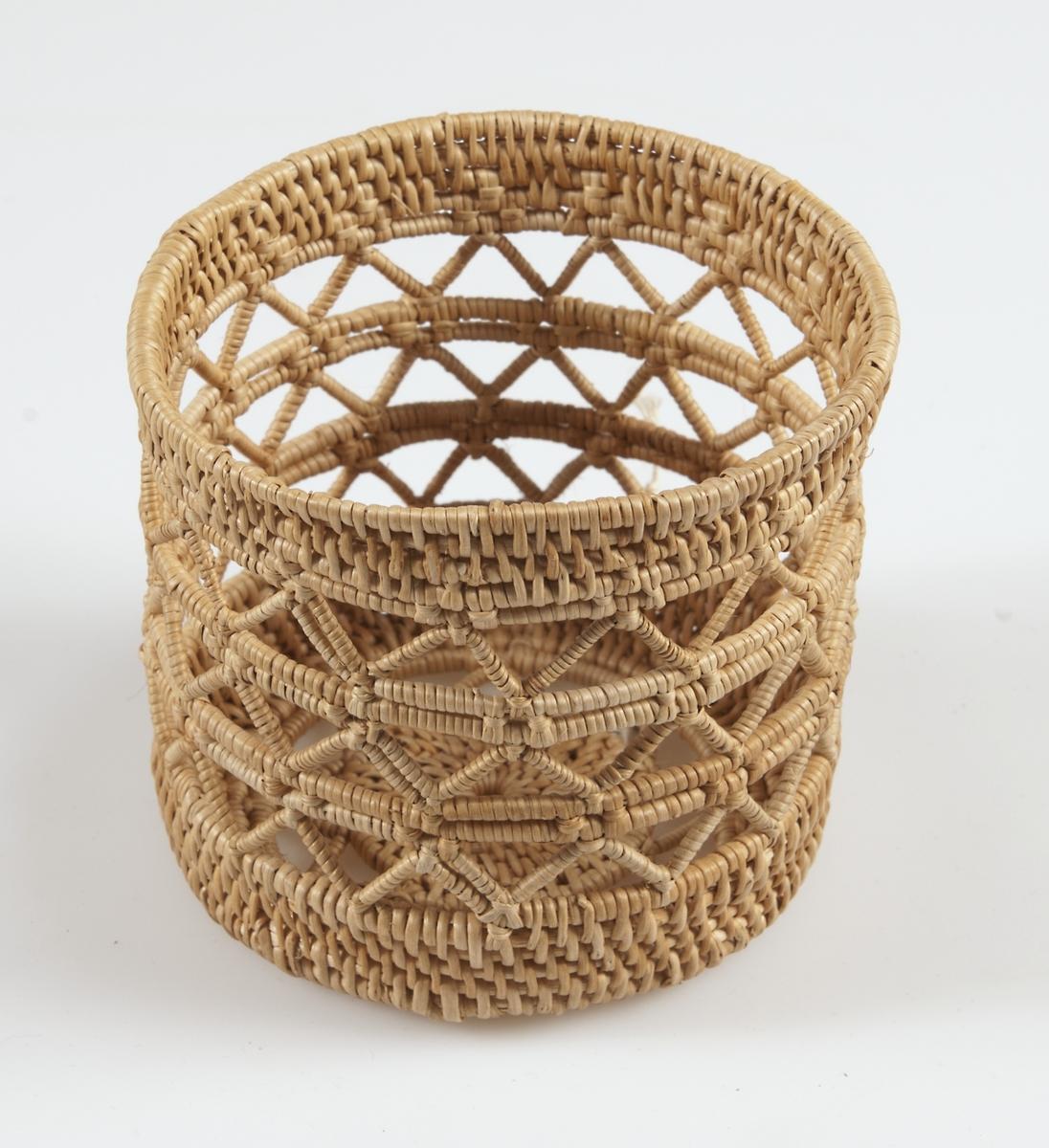 Korg av bundna björkrötter, cylinderform, genombrutet zig-zagmönster runt mitten och i botten. Tillverkad av Gertrud Nilsson.