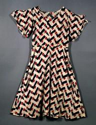 Kortärmad sommarklänning av bomullsvoile med tryckt nonfigurativt mönster i svart och rött mot ljus botten. Resårtunnel i midjan. Djup rund urringning med infällt V-format parti fram. Insyningar från axeln. Isydd vingärm som är nästan helt öppen från axeln. Den bakre vingen är längre än den främre. Kjolen skuren i två våder med infällda kilar i sidorna.