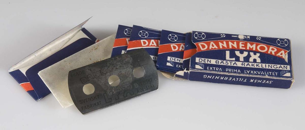 Rakbladsförpackning, liten ask av papp, blå med rött band och text i vitt och blått: Dannemora Lyx, Den bästa rakklingan, Extra prima kvalitét, Svensk Tillverkning, 5 blad. Upptill ser man ett hammarhuvud flankerat av drivhjul och -remmar. Asken innehåller 5 rakblad i obrutna emballage, med samma tryck som asken.