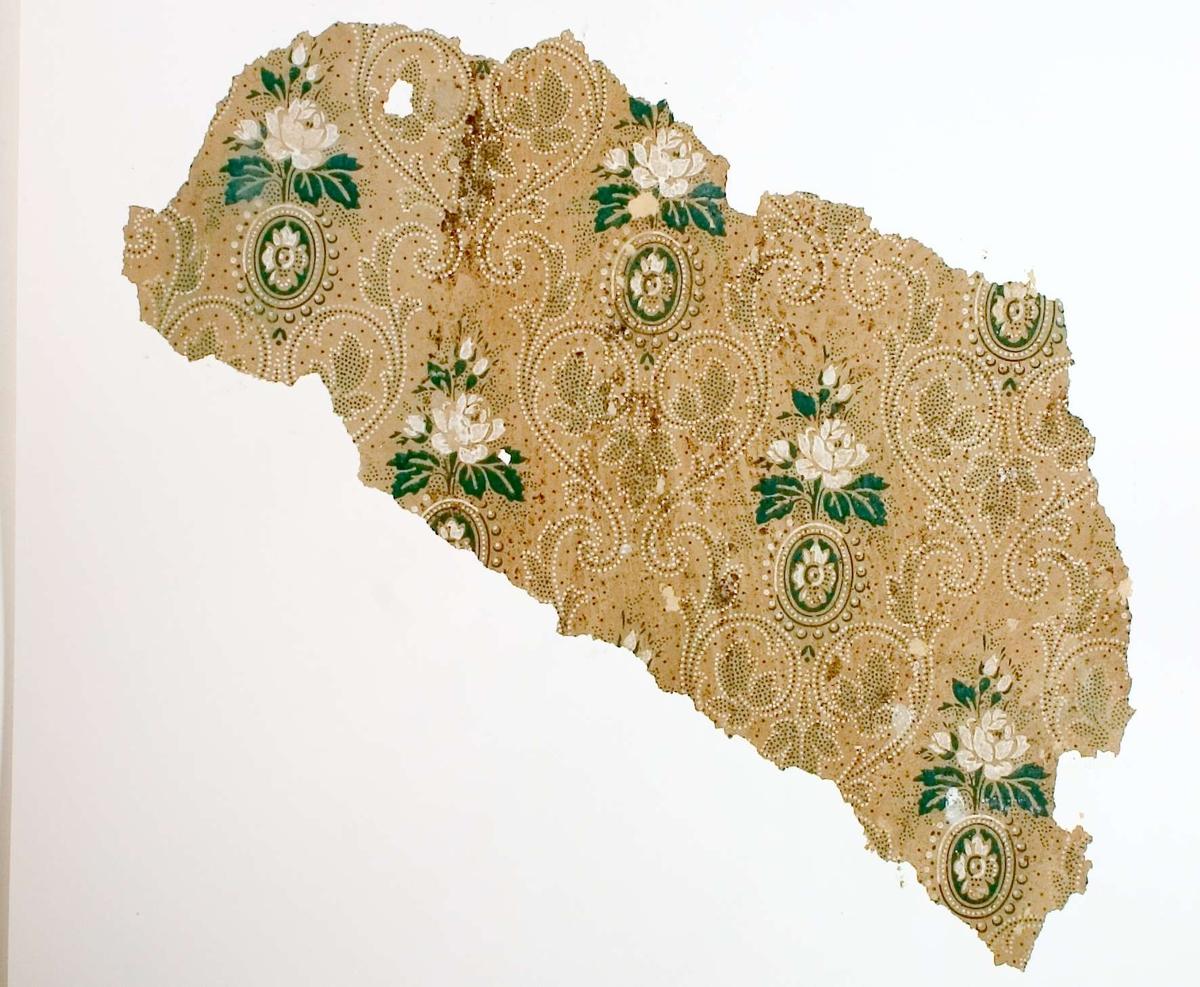 Tapetprov med tryckt blad- och blommönster i färgerna brungult, grönt och vitt.