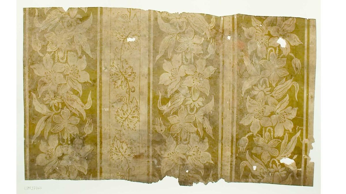 Tapetprov med tryckt mönster, gröngult och beige. Handskriven text på baksidan av kartongen: Nr  32 Kv. Svan nr 3 Klostergatan 15 Boningshus mot gatan  b.v. rum 1 1.