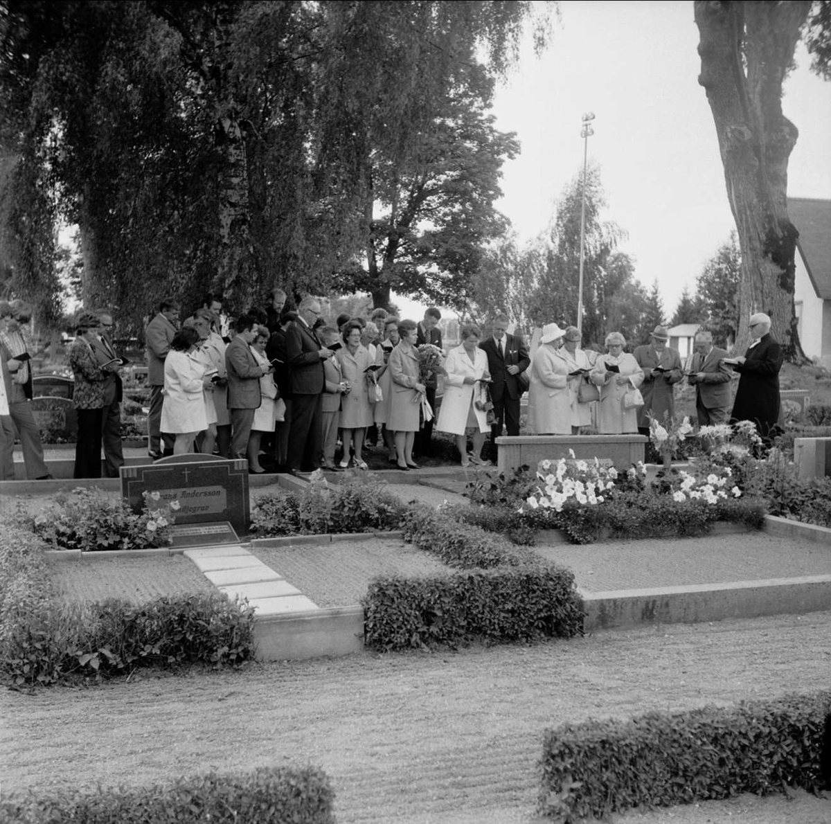 Släkt- och kusinträff på Tierps kyrkas kyrkogård, Uppland september 1972. Grupp samlad framför grav