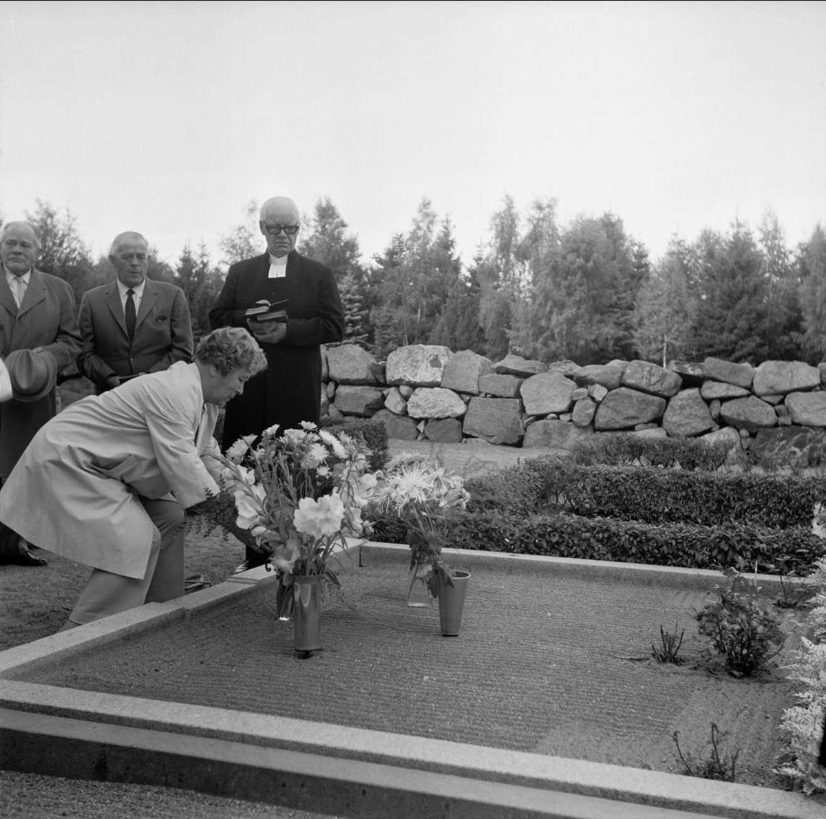 Släkt- och kusinträff på Tierps kyrkas kyrkogård, Uppland september 1972. Kvinna placerar blommor på grav
