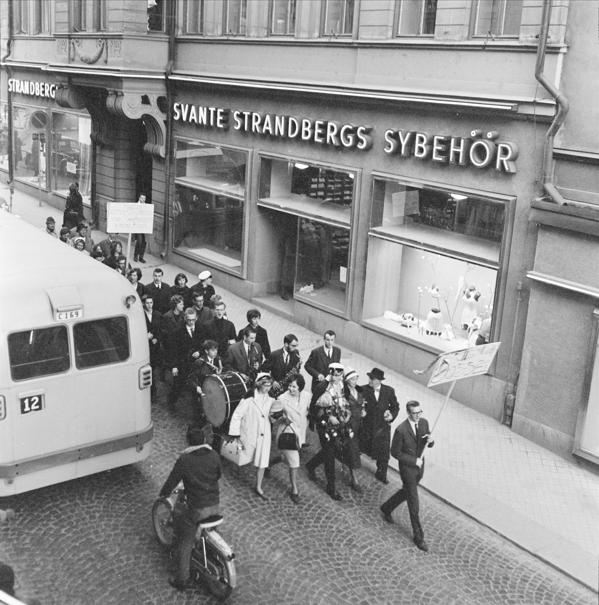 Studentfirande på Drottninggatan utanför Strandbergs sybehörsaffär, kvarteret Näktergalen, Dragarbrunn, Uppsala 1962