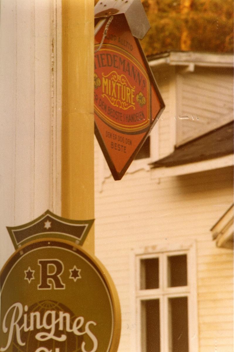Reklameskilt på fasaden til forretningen N. G. Rudi.