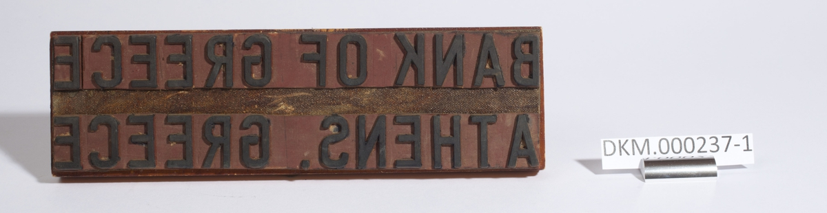 Stempelet er festet under en smal, rektangulær treplate med håndtak. Speilvendt står det: BANK OF GREECE                                ATHENS. GREECE