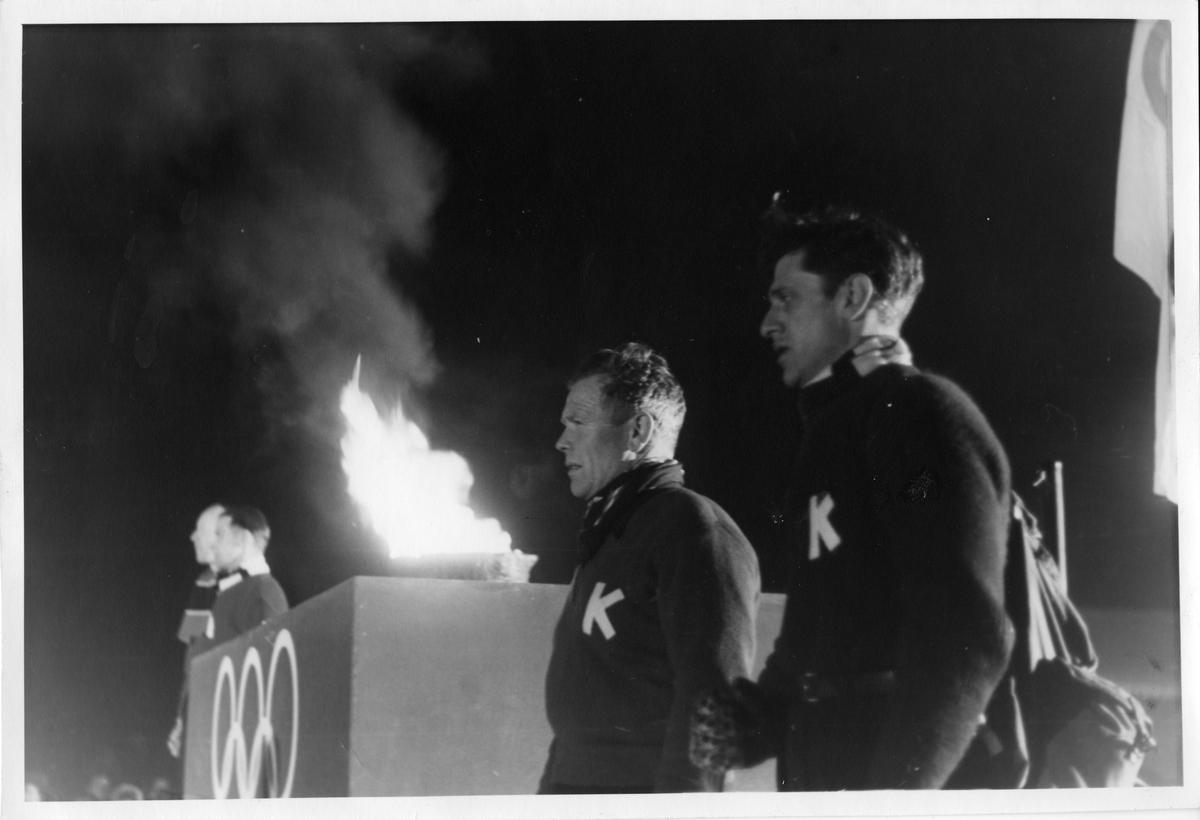 Arnholdt Kongsgård (t.v.) og Petter Hugsted under fakkelseremoni på Kirketorget på Kongsberg i forbindelse med OL 1952. Arnholdt Kongsgård and Peter Hugsted during the tourch ceremony in Kongsberg 1952.