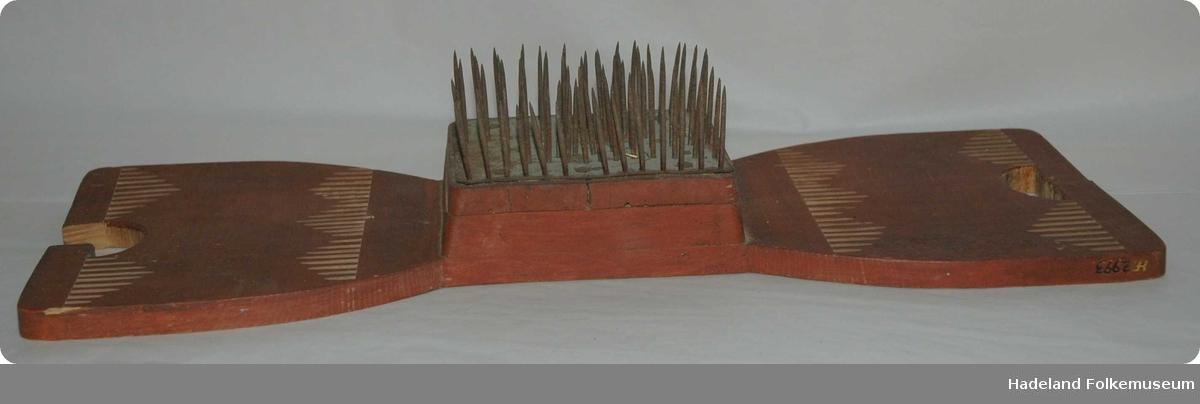 Rektangulær treplate som er noe innsnevret på midten. Et hull i hver ende fungerer som håndtak. Midt på platen er det et trestykke som danner base for en firekantet metallplate med jernpigger som står opp. Utskjært stavbord. Ødelagt i ene håndtaket.