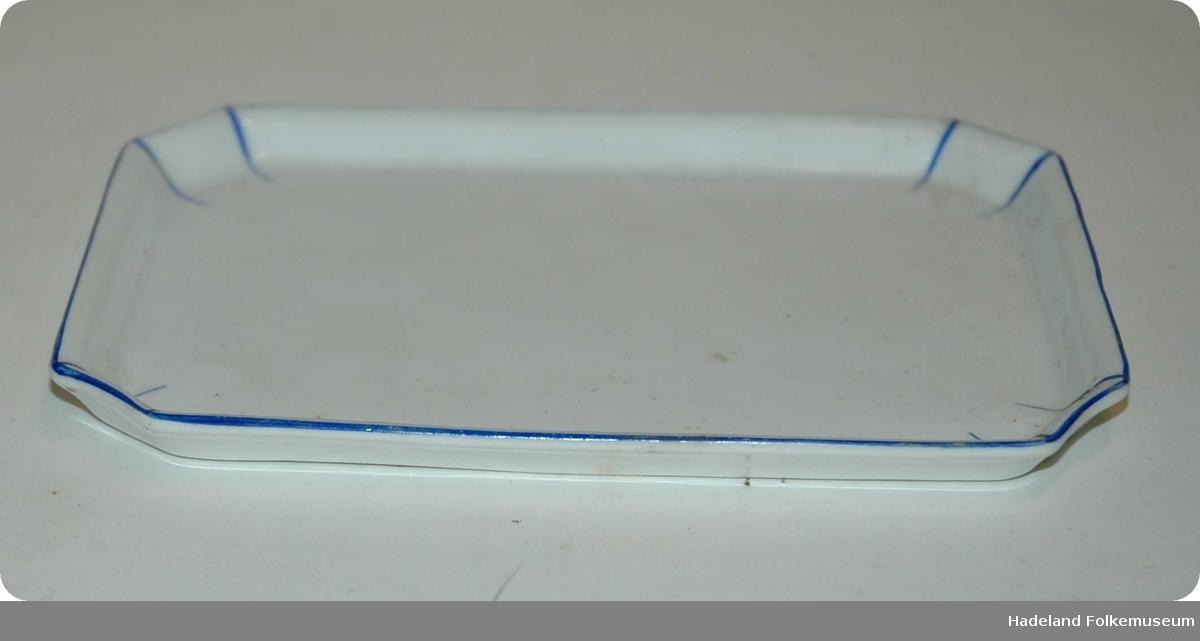 Hvitt steintøy med blå stripedekor. Rektangulært grunnplan med skrå hjørner. Kantene er utoverskrånende. Ikke glassert under.