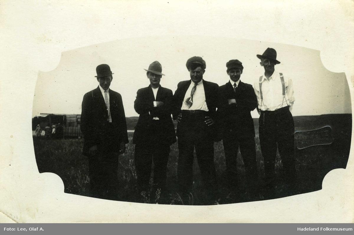 Fem menn oppstilt på rekke, med dress og hodeplagg