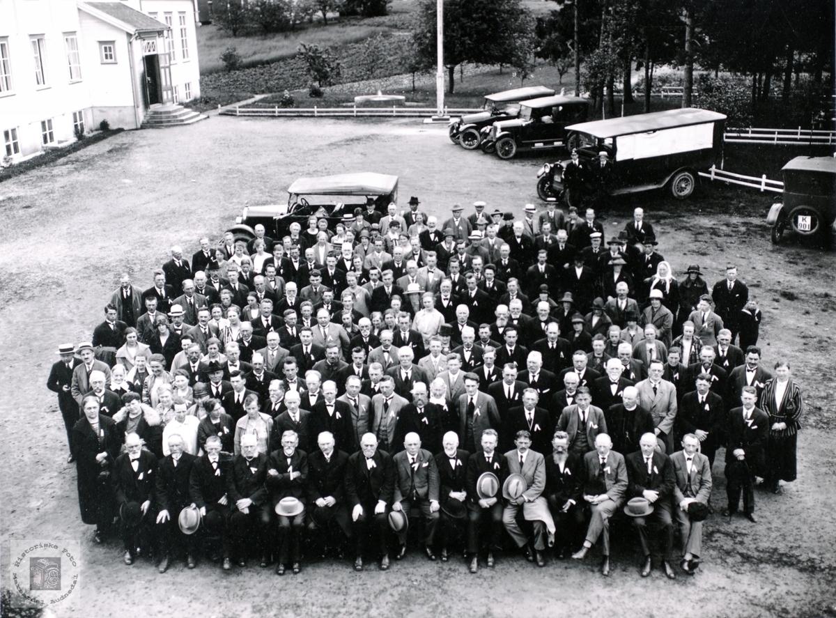 Portrett av stor gruppe med kjøretøy fra 1920 tallet i bakgrunnen.