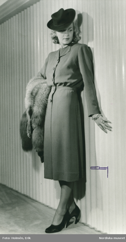 Helporträtt av kvinna i kappa av Gaby Jouval, päls i handen.